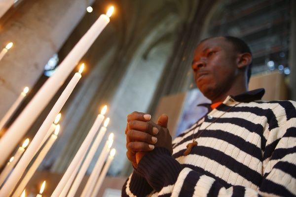 Man praying with candles in church. © Godong/UIG