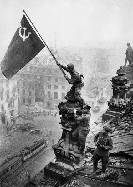 Red army soldiers raising the soviet flag over the reichstag in berlin, germany, april 30, 1945, photo taken by vladimir grebnev.. © Sovfoto/Universal Images Group