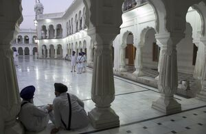 Two Sikhs priests at dawn sitting under arcades