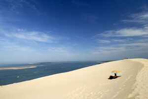 Tourists under a parasol on the Dune du Pyla, largest dune in Europe, Bay of Arcachon