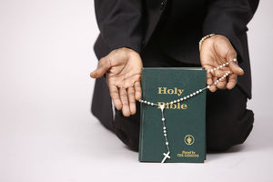 Evangelical christian holding a bible and prayer beads
