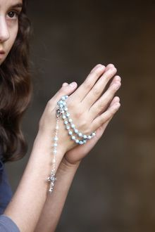 Girl praying with prayer beads