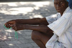 Haitian woman praying with prayer beads