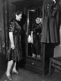 Nina lobkovskaya in war and peace, like all young girls, nina loves pretty clothes, here she is trying on a dress during a shopping trip, if it were not for her uniform with its decorations hanging nearby, no one would guess that she has been through the war, 1940s.