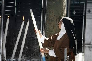 Nun lighting a candle at the Lourdes shrine